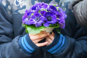 Een kleinkind houdt bloemen vast voor bij het graf van opa - contact